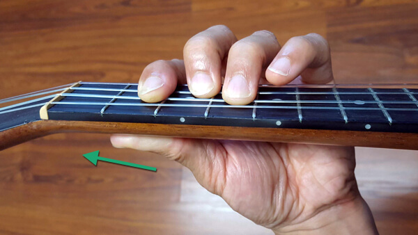 Ukulele bar chord thumb pointing toward headstock